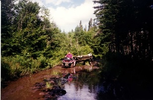 Robert Walsh towing wing on trailer with ATV on the trail from the lake