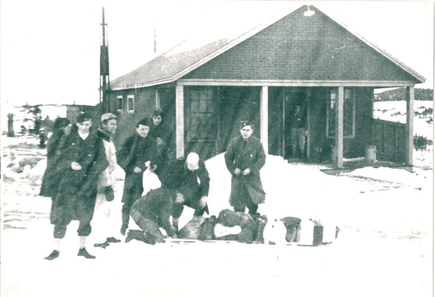 "Small group of airmen prepared to walk across the ""Barrens"" home for Christmas leave. Foreground Marvin Miller behind the group, Norman Paquet at the right, behind the toboggan buttoning his coat. Man with the white cap is Ed Flowers watching Mickey Stevens attaching the luggage to the toboggan."